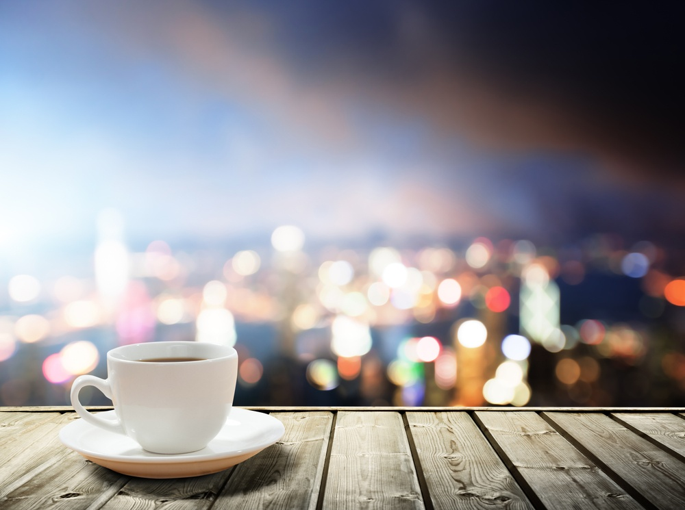 A cup of coffee and the twinkling, evening lights of the cityscape in the background provide a perfect scene for contemplating realized versus recognized gains.