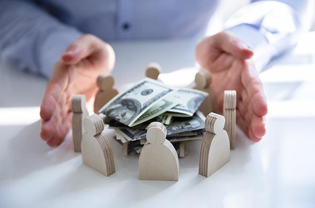 man-hands-figures-money-pile-IS-1146964352