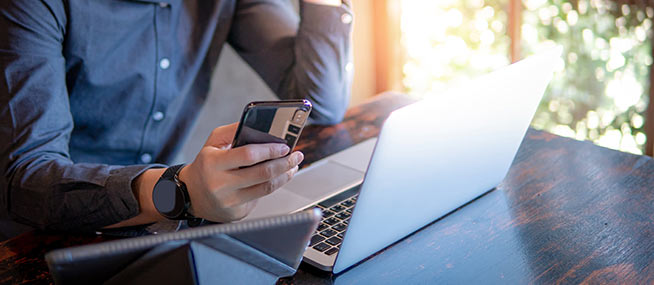 man-holding-phone-with-laptop-IS-1130938108