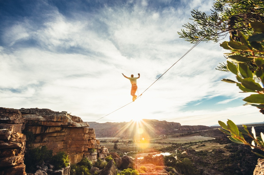 A man on a tightrope, halfway through his journey over a valley, symbolizes the risk of NNN investing.