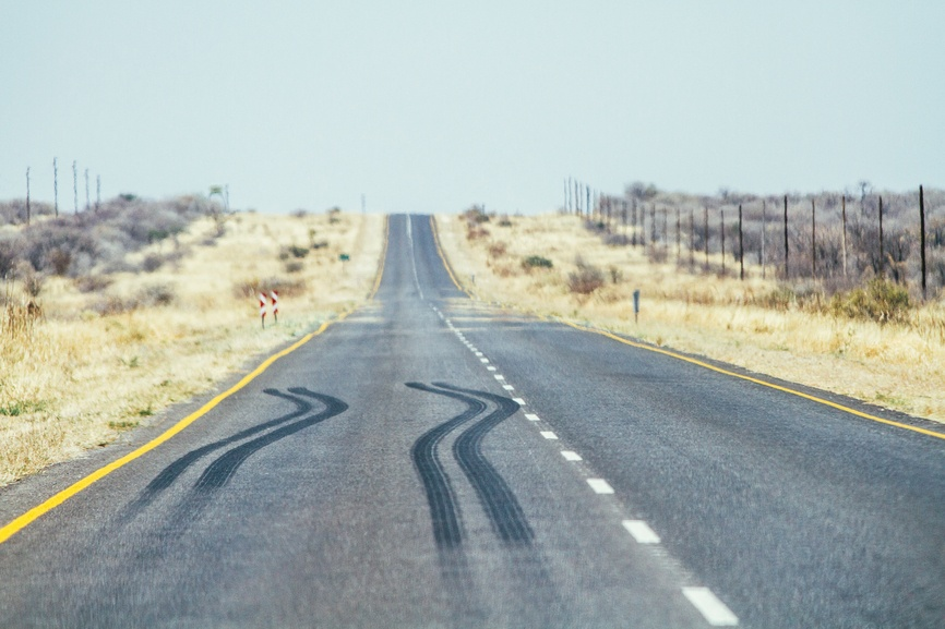 An empty road stretches out, with a clear set of skid marks, signifying the abrupt stop that will happen to your 1031 exchange when your qualified intermediary goes bankrupt.