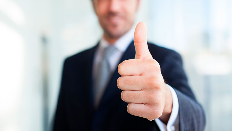 Business man giving the thumbs up on tax benefits of real estate investing